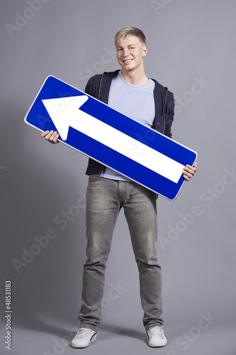 Joyful man holding direction arrow sign.