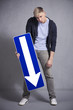 Miserable man holding direction arrow sign pointing down.
