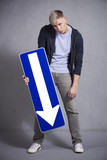 Miserable man holding direction arrow sign pointing down. poster