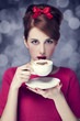 Redhead girl with coffee cup. St. Valentine's Day.