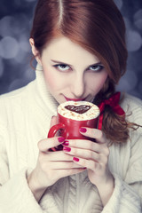 Redhead girl with red coffee cup. St. Valentine Day