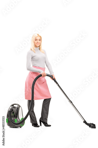 Full length portrait of a blond housewife cleaning with a vacuum