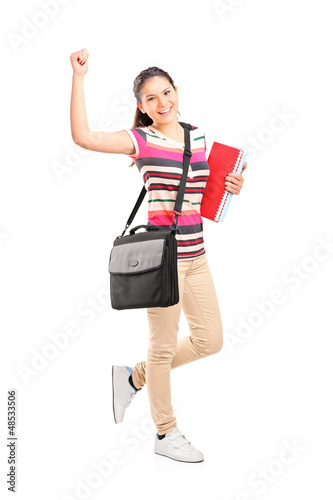 Full length portrait of a happy female student holding notebooks