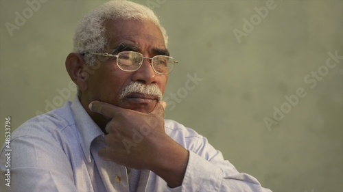 Portrait of serious black old man with glasses looking away