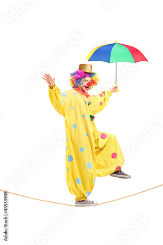 Happy male clown with umbrella walking on a rope