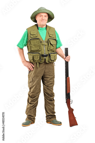 Full length portrait of a male hunter holding a shotgun