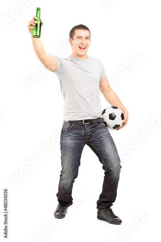 Euphoric sport fan holding a beer bottle and football