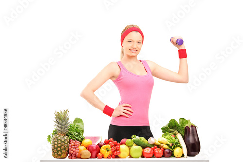Young woman holding a dumbbell and posing with a pile of food