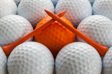 An closeup of a regular a orange golf tees on a golf balls