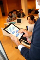 Teacher using tablet to make business presentation