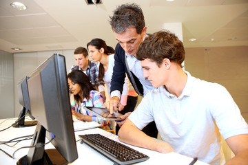 Adult man helping student in classroom