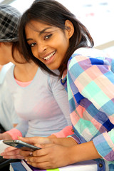 Smiling teenage girl with smartphone