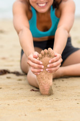 Foot and stretching concept on beach