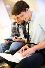 Boys using laptop computer in school building