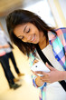 Cheerful student girl writing message on smartphone