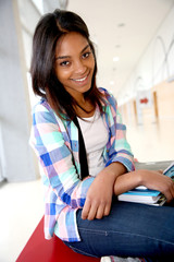 Cheerful student girl sitting on school bench