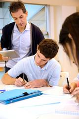 Teacher watching students writing exam