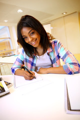 Portrait of student girl writing on notebook