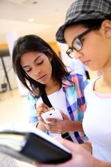 Girlfriends in hallway using smartphone