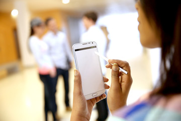 Backview of smartphone screen held by student