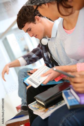 Teenagers using smartphones in school corridor