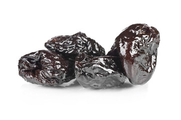 Dried prunes over a reflective white background