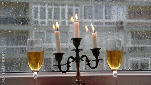 Lighted candles and raindrops on the window