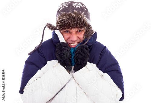 Young man with hat and coat  shivering  from cold