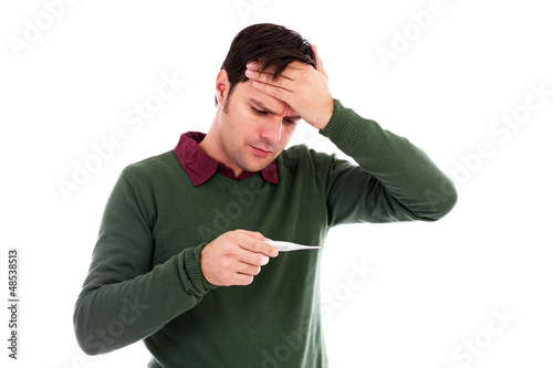 Young man suffering from a cold and checking his temperature on
