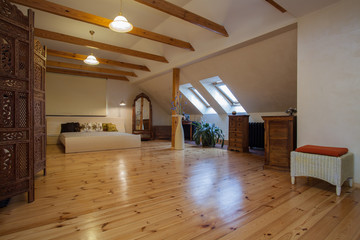 Cloudy home - attic with a pine wood floor