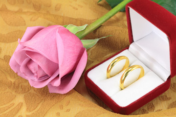 A pair of wedding rings and a pink rose