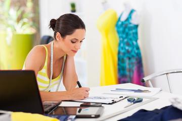 pretty female fashion designer drawing new designs