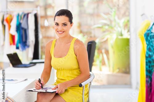 beautiful female dressmaker drawing new design in studio