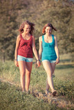 Two Beautiful Teenage Girls Walking at Park