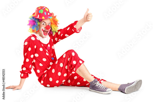 A clown with smiling joyful expression sitting down and giving t
