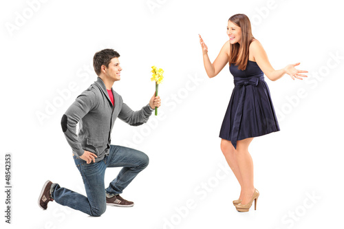 A male kneeling with flowers and his excited girlfriend