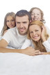 family smiling while laying on bed covered with white linen