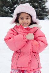 Happy East Indian girl playing in the snow