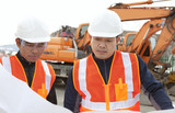 construction worker with heavy equipment on the background