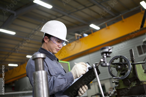 mechanical technician writing on notepad