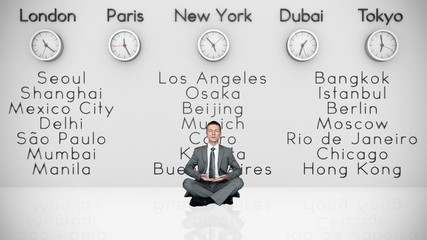 Businessman Meditating with World Clocks and Big Cities