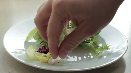 A chef loads up a plate with green salad