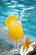 Jus de fruit orange au bord d'une piscine