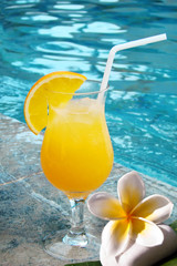Jus de fruit orange au bord d'une piscine