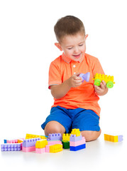 cheerful child boy playing with construction set over white back