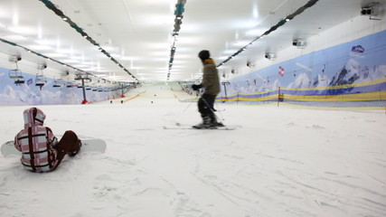 small boy with snowboard prepares for training in sport center