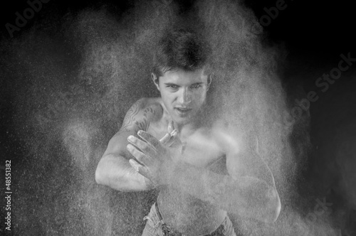 A dramatic   portrait of a athletic man in a spray of flour.