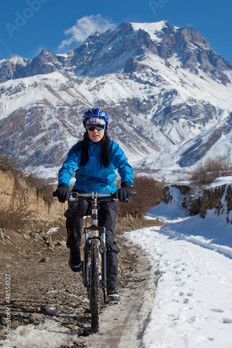 Woman cycling in Hymalaya mounains during sunny day