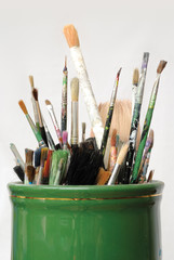 Used paint brushes in a green pot