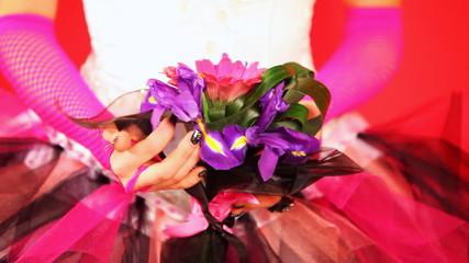 hands of bride in trendy wedding dress holding bouquet with iris